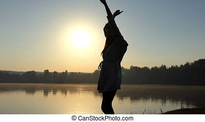 Happy young woman dances on a lake bank at sunset
