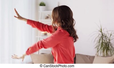happy young woman dancing at home