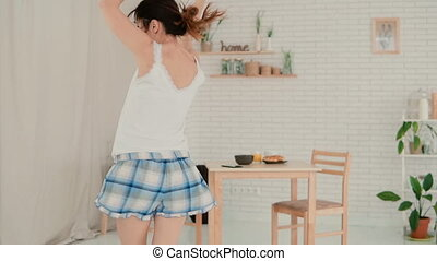 Happy young woman dancing in light kitchen wearing pajamas in the morning. Brunette girl having fun alone. Slow motion.