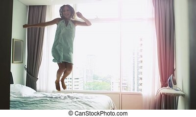 Happy young woman dancing jumping on bed at home having fun in the bed in a luxury apartment with city view and lens flare effects. slow motion. 3840x2160