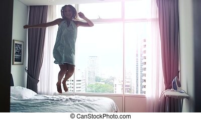 Happy young woman dancing, jumping on bed at home having fun in the bed in a luxury apartment with city view in Kuala Lumpur. slow motion. 3840x2160