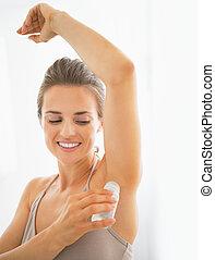 Happy young woman deodorant on underarm