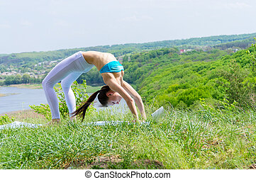 Happy young woman doing yoga on green river bank