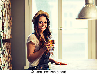 happy young woman drinking beer at bar or pub