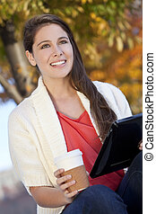 Happy Young Woman Drinking Coffee and Using Tablet Computer