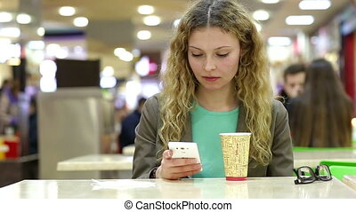 Happy young woman drinking coffee or tea and using mobile phone in a coffee shop