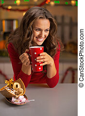 Happy young woman drinking cup of hot chocolate with christmas c