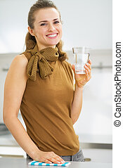 Happy young woman drinking water in kitchen