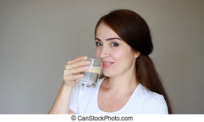 Happy young woman drinks a glass of water to stay healthy. Girl drinking and smiling. Close-up