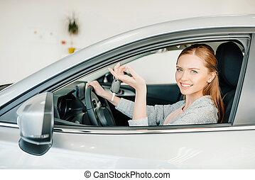Happy young woman driver sitting in new car and holding key
