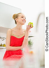 Happy young woman eating apple in kitchen