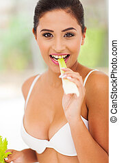 young woman eating celery stick