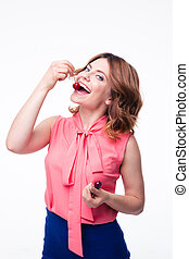 Happy young woman eating cherry