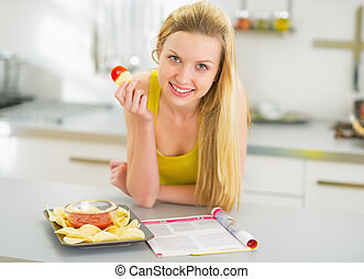 Happy young woman eating chips in kitchen