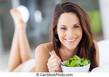 woman eating green salad on bed
