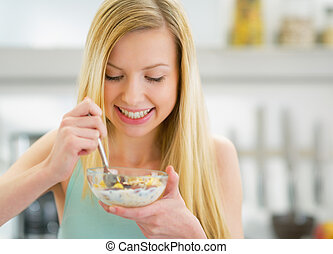 Happy young woman eating muesli in kitchen