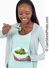 Happy young woman eating salad