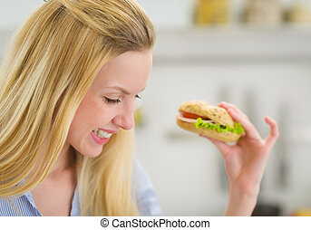 Happy young woman eating sandwich in kitchen
