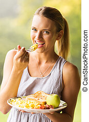 young woman eating scrambled eggs - happy young woman eating...