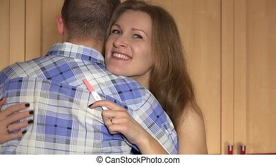 happy young woman embracing man after positive pregnancy test