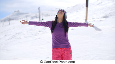 Happy young woman embracing the winter sun