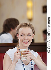 Happy young woman enjoying a cup of late macchiato