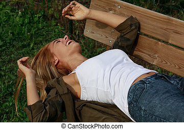 Happy young woman enjoying a good joke laughing heartily as she lies back relaxing on a wooden bench outdoors in the garden in evening light