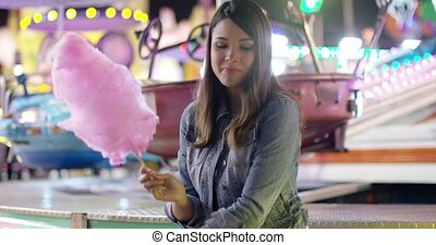 Happy young woman enjoying a night at a fairground or...