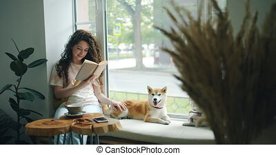 Happy young woman enjoying book and petting dog sitting on...