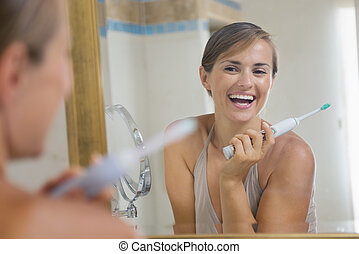 Happy young woman enjoying clean teeth after brushing electric teeth brush