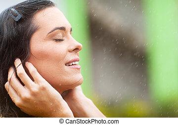 woman enjoying rain falling on her face