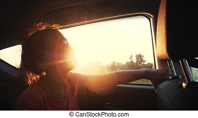 Happy young woman enjoys traveling by car in summer time. Sunset rays. Slow motion, sings song and dances.