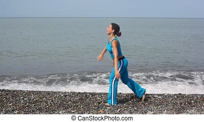 happy young woman exercising on pebble beach against sea