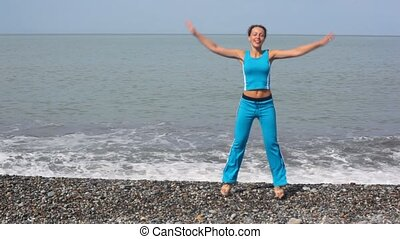 happy young woman exercising on pebble beach, sea in background