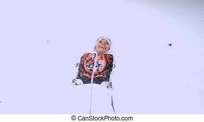Happy young woman falling down in snowdrift enjoying...