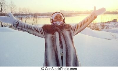 Happy young woman falling down in winter lying in snowdrift...