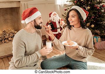 Happy young woman feeding her boyfriend