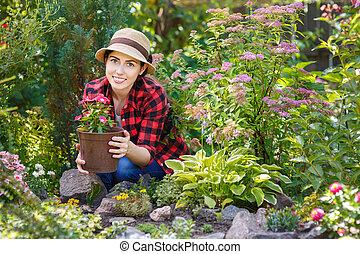 gardener holding flower in pot