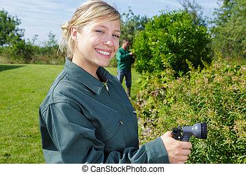 happy young woman gardener watering garden with hose
