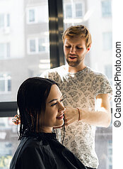 Happy young woman getting a new haircut by hairdresser at parlor