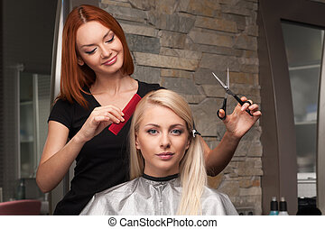 Happy young woman getting new haircut by hairdresser at parlor. redhead hairdresser cutting client's hair in beauty salon