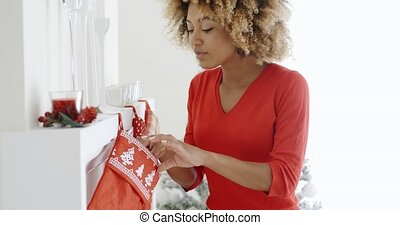 Happy young woman hanging Christmas stockings - Happy young...
