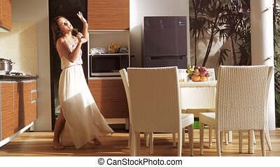 Happy young woman has fun singing and dancing in the kitchen...