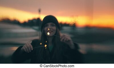 Happy young woman having fun with sparkler at the beautiful sunset