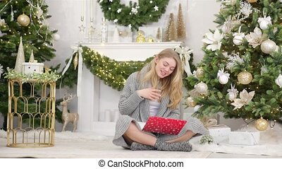 Happy young woman having video chat on laptop in christmas decorated living room