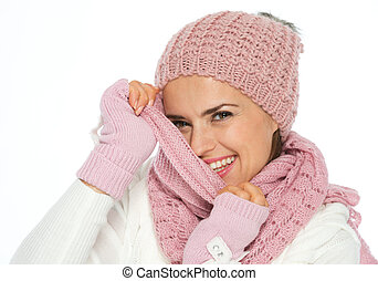 Happy young woman hiding behind knit scarf
