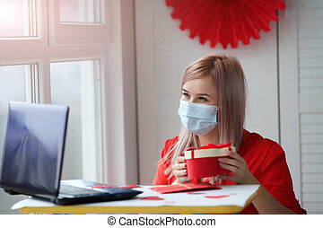 Happy young woman holding a box with a gift in a medical mask. Valentines Day ideas during the coronavirus outbreak.