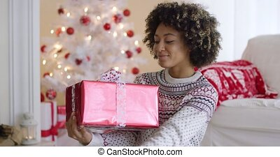 Happy young woman holding a Christmas gift