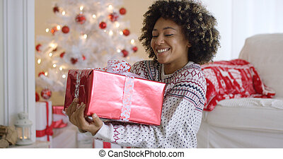 Happy young woman holding a Christmas gift looking down at...