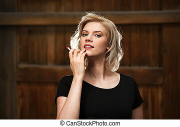 Happy young woman holding a lipstick
